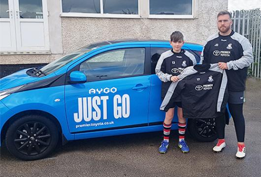Team Coach, Jonny, with one of the new training jackets. Pictured alongside player, Callum